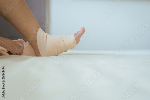 Fototapety, obrazy: Hands using elastic bandage with leg,Female putting bandage on his injured ankle