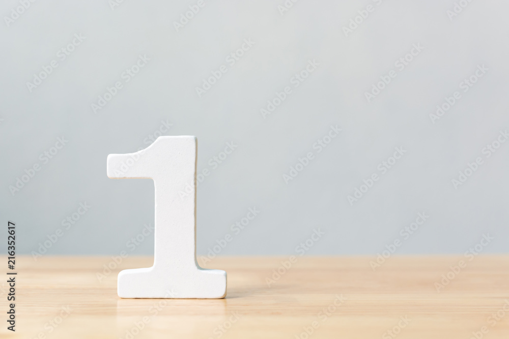 Fototapeta Number one wooden material on table. Concept top winner success with copy space
