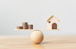 Leinwanddruck Bild - Wooden home and money coins stack on wood scale. Property investment and house mortgage financial real estate concept