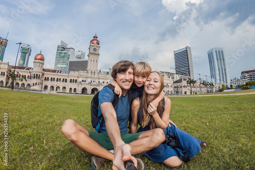 happy family makes selfie on the background on background of Merdeka square and Sultan Abdul Samad Building Canvas Print