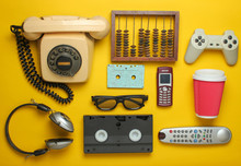 Retro Objects On A Yellow Background. Rotary Telephone, Audio Cassette, Video Cassette, Gamepad, 3d Glasses, Tv Remote, Headphones, Push-button Phone. Analog Media Technology Of The Past. Flat Lay..