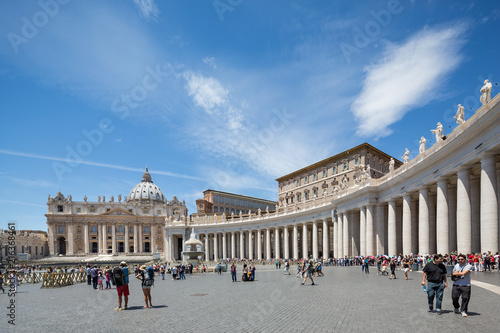 Statues on the colonnades and tourists in front of a fountain in St Peter's squa Fotobehang