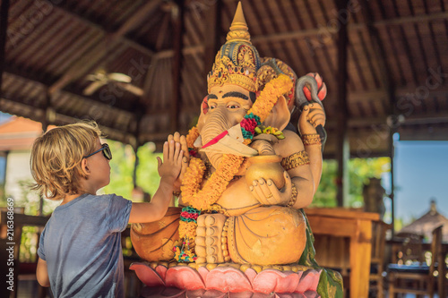 Caucasian boy high-five Ganesha. Meeting Western and Eastern culture concept. oriental and occidental. Traveling to Asia with children