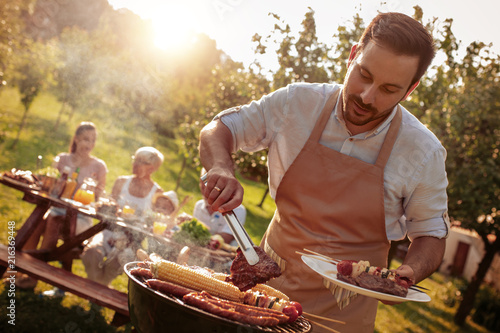 Family grilling meat on a barbecue Fototapet