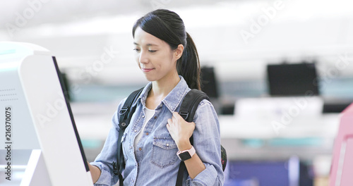 Photo Asian Woman using selfie check in machine in the airport
