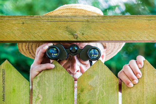 Cuadros en Lienzo a curious neighbor stands behind a fence and watches with binoculars