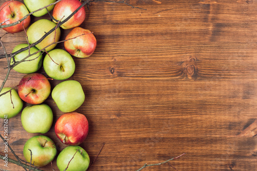 Sweet juicy red and green apples with branches on wooden background. Free copy space for text. Top view, flat lay
