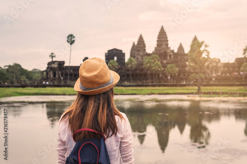 Poster Lieu connus d Asie Young woman traveler looking at Angkor Wat, Khmer architecture heritage in Siem Reap, Cambodia