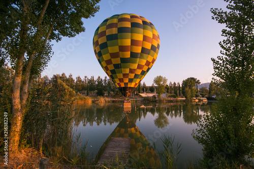 Mongolfiera colorata in volo sopra al lago - 216382249