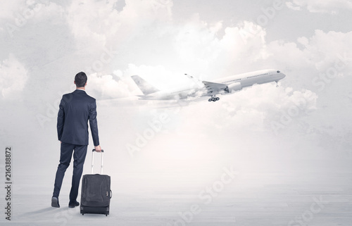 Young businessman with luggage walking towards to a raising airplane Fototapet