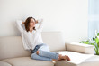 Happy young woman enjoying sunny morning lying on cozy sofa in modern apartment, smiling female relaxing on couch planning day off, calm girl stretching on couch resting and spending weekend at home
