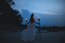 Bride In Beautiful Wedding Dress Is Holding Torchlight On The Beach
