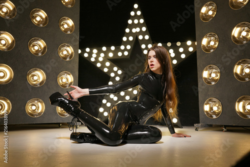 Canvas Print hot kinky woman wearing latex rubber catsuit and fetish corset posing in the bla
