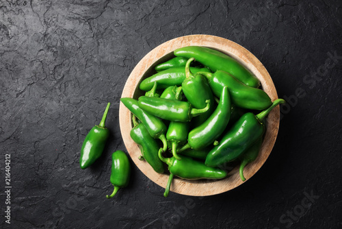 Poster Hot chili peppers Green jalapeno hot pepper in wooden plate closeup. Food photography