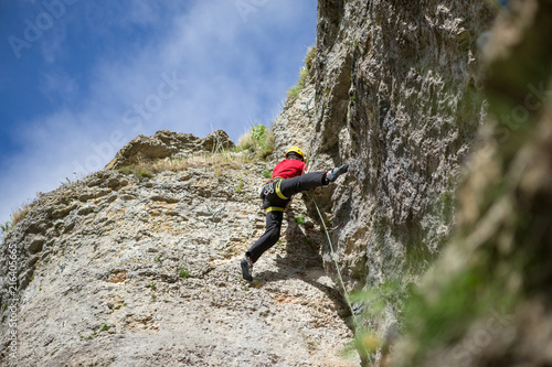 Poster  Photo from back of climbing young sports guy in yellow helmet on rock at summer