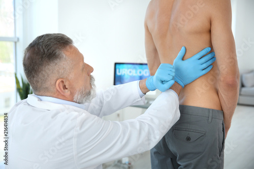 Fotografía  Urologist in gloves examining young patient in clinic