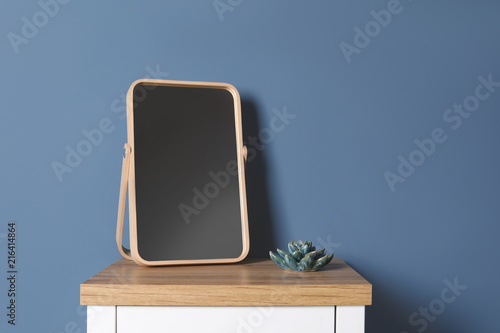 Modern mirror on table near color wall