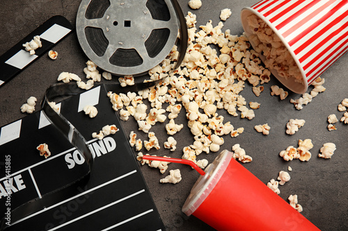 Flat lay composition with popcorn, film reel and clapperboard on grey background