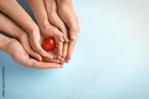 Fotografia Family holding small red heart in hands on color background
