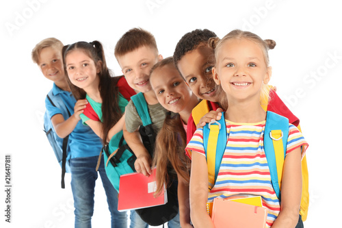Fotografía  Group of little children with backpacks and school supplies on white background