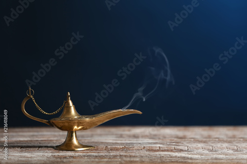 Aladdin lamp of wishes on wooden table against dark background Canvas Print
