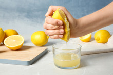 Woman Squeezing Lemon Juice In...