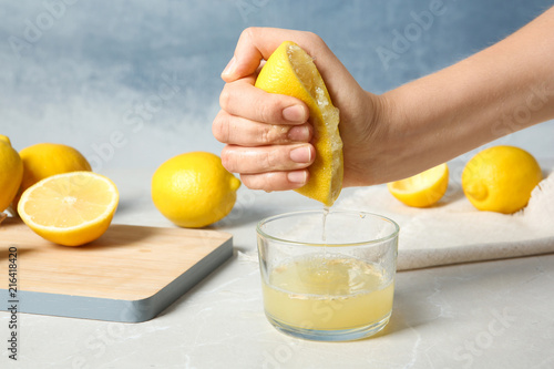Woman squeezing lemon juice into glass on table