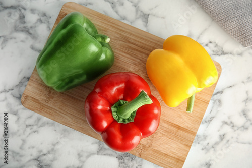 Fotografija Wooden board with ripe paprika peppers on marble background, top view