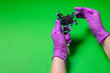 Leinwanddruck Bild - Hands Hold A Blue Tattoo Machine