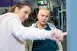 elderly man worming up at gym with female trainer