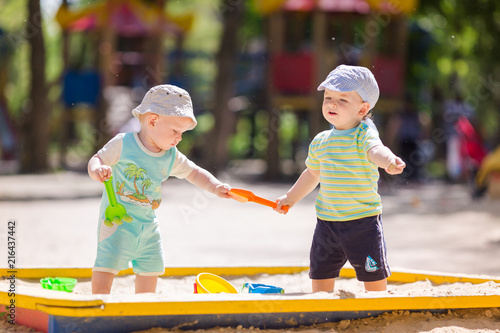 Obraz na plátně Two baby boys playing with sand