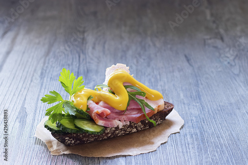 Obraz na płótnie Sandwich with ham, fresh cucumber and mustard on brown paper.