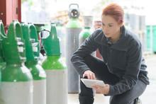 Female Worker Checking Oxygen Bottles