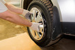 A mechanic removing the hubcap from a car wheel. Tire fitting. Tire service.