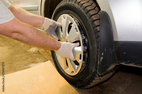Fotografie, Obraz  A mechanic removing the hubcap from a car wheel