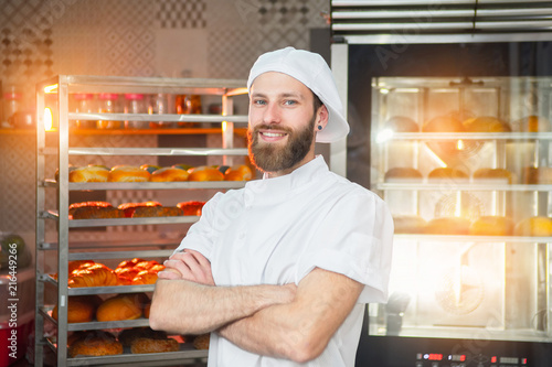 Fotografía  Portrait of a young beautiful baker with fresh bread and an oven in the backgrou