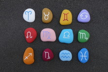 Astrological Signs With Stylized Colored Stones Over Black Volcanic Sand