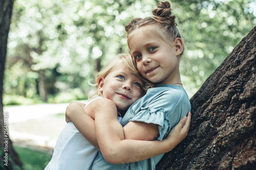 Fototapeta Waist up portrait of delighted small girls standing by tree and hugging