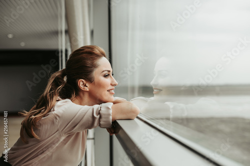 Fototapeta Side view happy woman dreaming while looking at window indoor. She having rest during labor obraz
