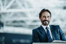 Portrait Of Beaming Bearded Male Having Job Indoor. He Looking At Camera. Positive Employer Concept. Copy Space