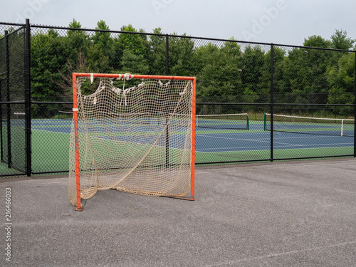 Fotografiet  Offseason, beat up, rusted, ragged lacrosse goal sitting on asphalt court with n