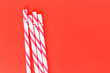 canvas print picture - red striped straws on pink background