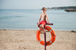 healthy little boy in sunglasses sitting on beach with lifebuoy in summer day