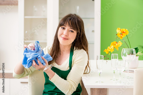 Fotografie, Tablou  Young woman cleaning glasses at home