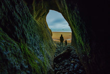 Mom And Son Looking Out Of Cave Out To The Ocean