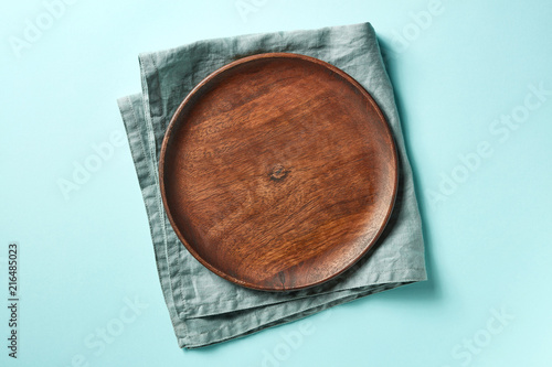 Wooden plate on blue background, from above