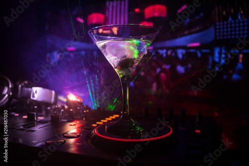 Glass with martini with olive inside on dj controller in night club. Dj Console with club drink at music party in nightclub with disco lights. Close up view - 216487030
