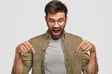 Wow, That`s Amazing! Amazed Shocked Young Male Looks With Surprisement Down, Points With Both Index Fingers, Dressed Casually, Opens Mouth Widely In Astonishment, Isolated Over White Background
