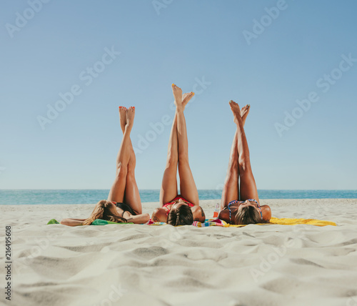 Poster Hoogte schaal Woman in bikini sunbathing on beach with legs raised to the sky