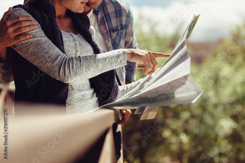 Deurstickers Couple looking for travel destination on map
